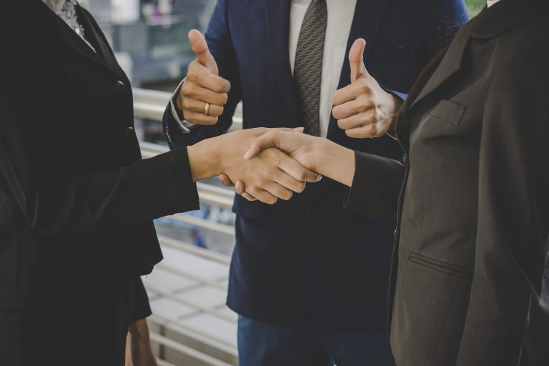 Business people shaking hands, finishing up meeting deals. Busin